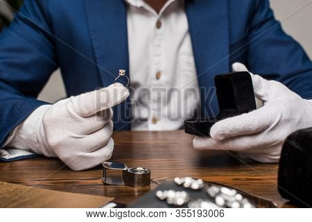 Cropped View Of Jewelry Appraiser Holding Ring With Gemstone And Box On Table On Grey Background