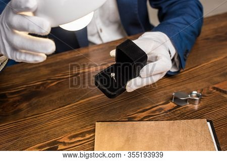 Cropped View Of Jewelry Appraiser Holding Ring With Gemstone In Box Near Lamp At Table Isolated On G