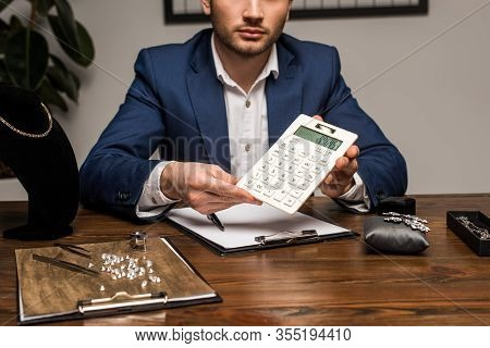 Cropped View Of Jewelry Appraiser Showing Calculator Near Clipboard And Jewelry On Table