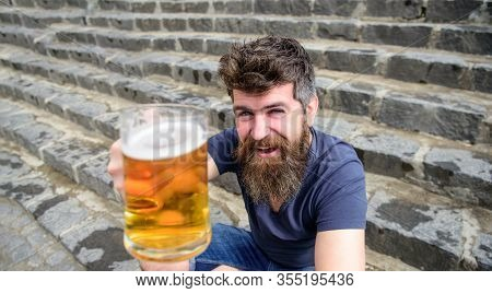 Hipster On Cheerful Face Drinks Beer Outdoor. Celebration Concept. Guy Raising Up Glass With Draught