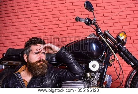 Bikers Lifestyle Concept. Hipster, Brutal Biker On Pensive Face In Leather Jacket Sits, Leans On Mot