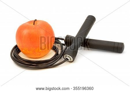 A Red Apple And Black Skipping Rope Isolated On White For Health And Fitness Concepts.
