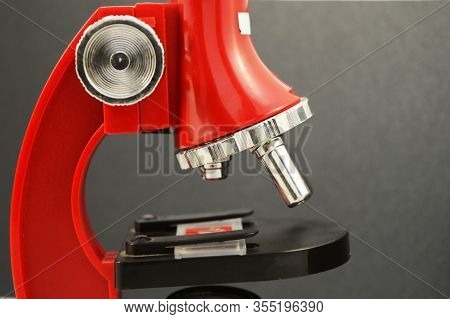 A Closeup On A Red Microscope Over A Black Gradient Background.