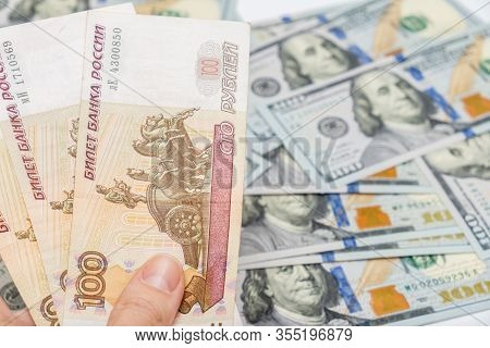 A Hand Holding One Hundred Ruble And American Dollar Banknotes On Background, Ruble Devaluation And