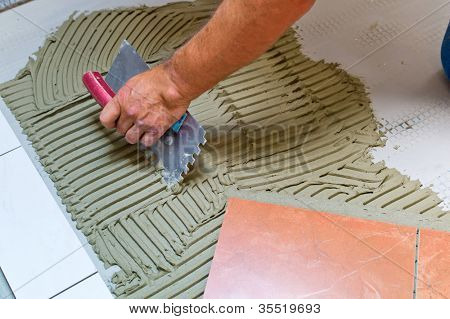 a tiler at work. bonding of floor tile with tile adhesive and filler.