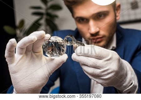 Selective Focus Of Jewelry Appraiser In Gloves Examining Gemstone With Magnifying Glass In Workshop