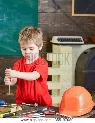Concentrated Kid Binding Screw To Wooden Board With Both Hands. Blond Boy Working In Repairs Worksho