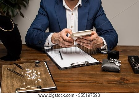 Cropped View Of Jewelry Appraiser Using Calculator Near Clipboard And Jewelry On Table