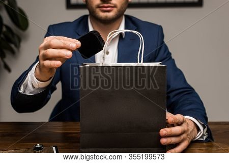 Cropped View Of Jewelry Appraiser Holding Box Near Paper Bag On Table