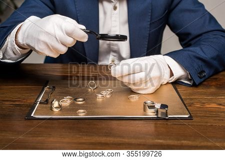 Cropped View Of Jewelry Appraiser With Magnifying Glass Examining Jewelry Ring Near Board On Table O