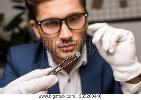 Selective Focus Of Jewelry Appraiser Holding Gemstone In Tweezers While Working In Workshop