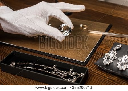 Cropped View Of Jewelry Appraiser Holding Gemstone Near Jewelry On Board On Table Isolated On Grey