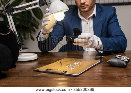 Cropped View Of Jewelry Appraiser Holding Ring With Gemstone In Box Near Lamp At Table
