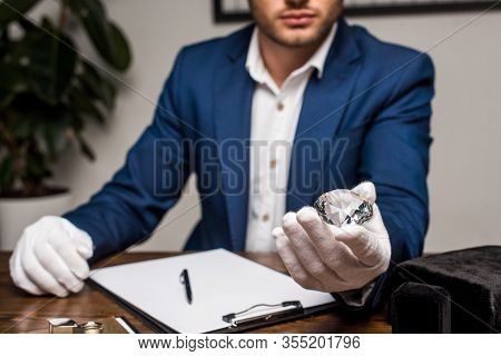 Selective Focus Of Jewelry Appraiser Holding Gemstone Near Clipboard On Table