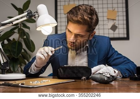 Handsome Jewelry Appraiser Examining Gemstone In Pliers Near Jewelry On Table In Workshop