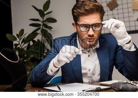 Jewelry Appraiser In Eyeglasses Examining Gemstone Near Calculator And Clipboard On Table In Worksho