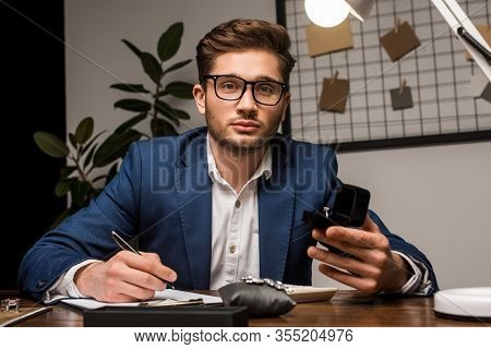 Jewelry Appraiser Looking At Camera While Holding Box With Ring And Writing On Clipboard Near Jewelr
