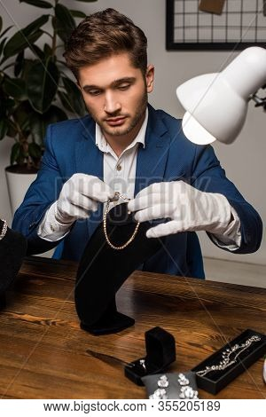 Handsome Jewelry Appraiser In Gloves Holding Necklace Near Necklace Stand And Jewelry On Table