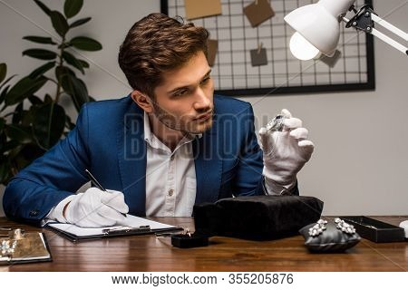 Jewelry Appraiser In Gloves Holding Gemstone While Writing On Clipboard Near Jewelry On Table In Wor