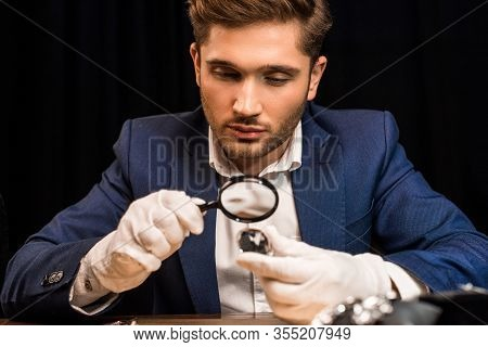 Jewelry Appraiser Holding Gemstone And Magnifying Glass Near Jewelry On Table Isolated On Black