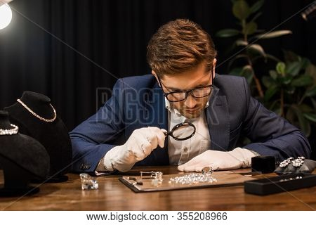 Handsome Jewelry Appraiser Examining Gemstones On Board With Magnifying Glass On Table