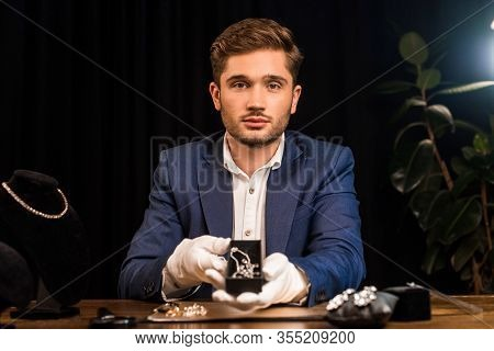 Jewelry Appraiser Looking At Camera And Holding Necklace Near Jewelry On Table In Workshop