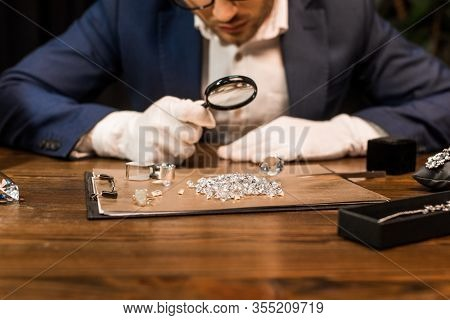 Cropped View Of Jewelry Appraiser Examining Gemstones On Board Near Jewelry On Table Isolated On Bla