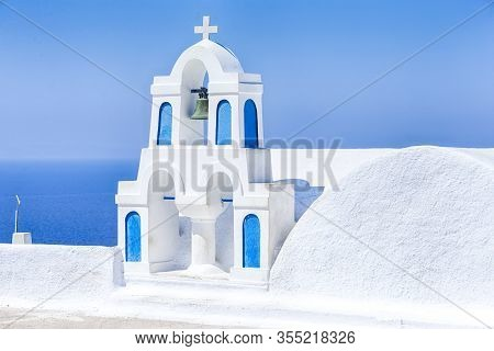 Traveling Ideas And Concepts. View Of Traditional Blue And White Greek Church With Bell And Cross In