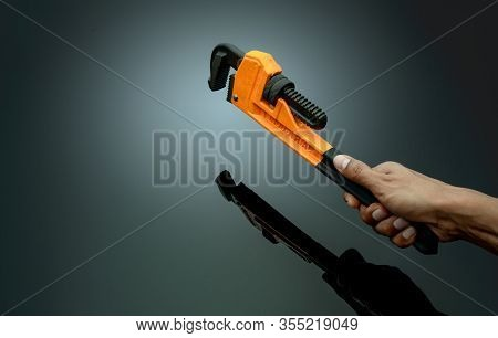 Plumber Hand Holding Handle Of Chrome Pipe Wrench Isolated On Dark Background. Metal Monkey Wrench F