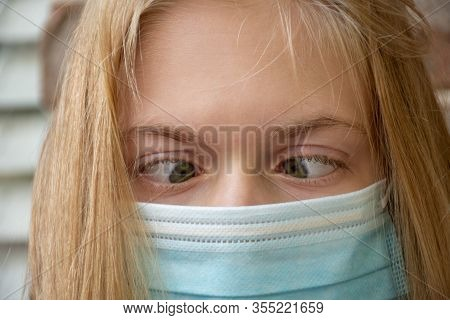 A Girl Wearing Disposable Surgical Face Mask Making Funny Silly Face. Coronavirus Concept