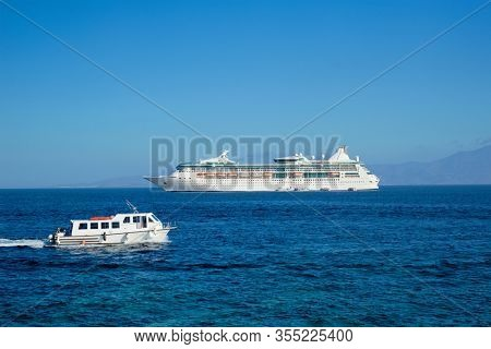 Boat and cruise liner is Aegean sea on beautiful summer day. Chora, Mykonos island, Greece