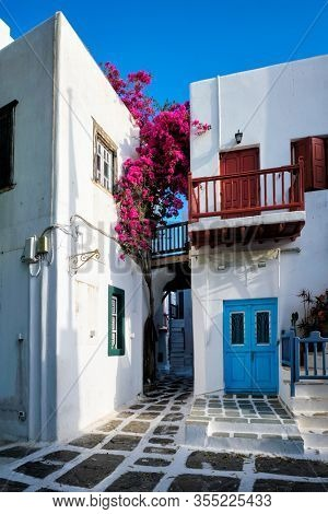 Picturesque scenic narrow streets with traditional whitewashed houses with blue doors windows of Mykonos Chora town in famous tourist attraction Mykonos island, Greece
