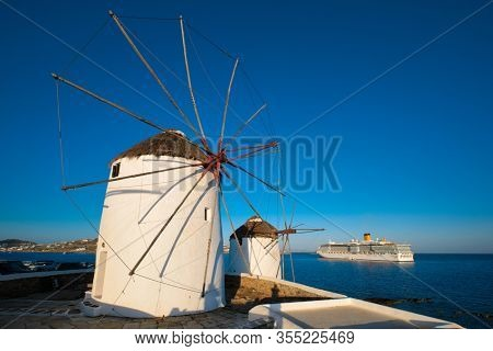 Scenic view of famous Mykonos town windmills. Traditional greek windmills on Mykonos island at sunrise with cruise ship in background, Cyclades, Greece