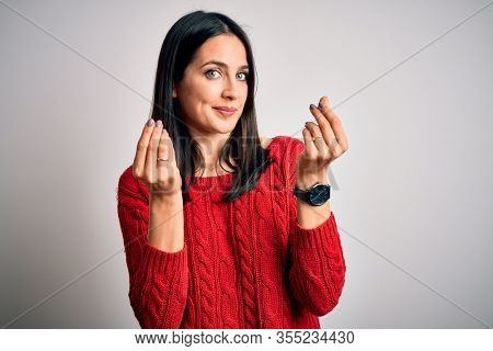 Young brunette woman with blue eyes wearing casual sweater over isolated white background doing money gesture with hands, asking for salary payment, millionaire business