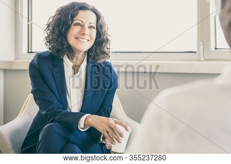 Happy Female Coworkers Chatting During Coffee Break. Business Woman Sitting In Armchair, Holding Cof