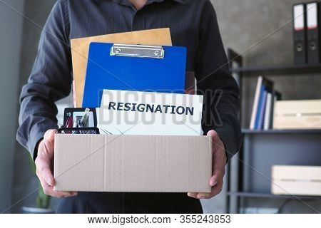 Businessmen Are Lifting Brown Paper Boxes That Collect Personal Items And Resignation Letters. The C