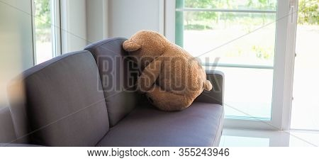 Child Concept Of Sorrow. Teddy Bear Sitting Leaning Against The Wall Of The House Alone, Look Sad An