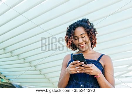 Happy Pensive Woman Typing Message On Cell Outside. Young Mix Raced Woman Using Mobile Phone, Lookin