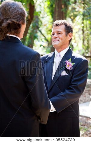 Handsome hispanic groom marrying his same sex partner in an outdoor wedding ceremony.