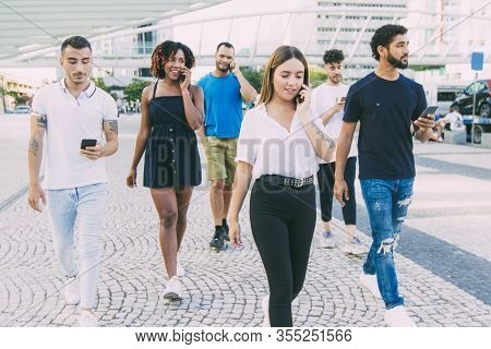 Multiethnic Group Of People With Smartphones Walking Through City Square. Mix Raced Men And Women Go