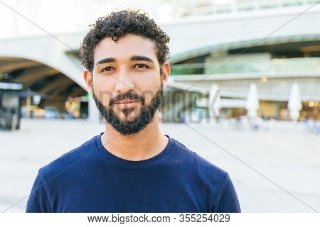 Pensive Positive Mix Raced Guy Posing In City Square. Front Portrait On Young Man With Black Curly H