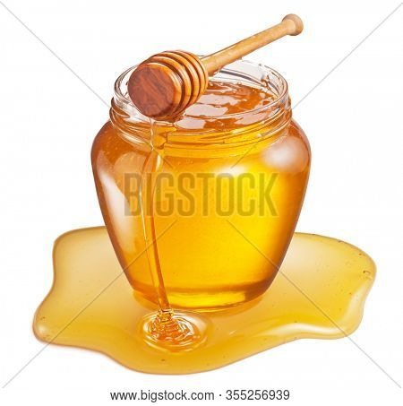 Glass pot of honey and sweet sticky honey puddle isolated on white background.