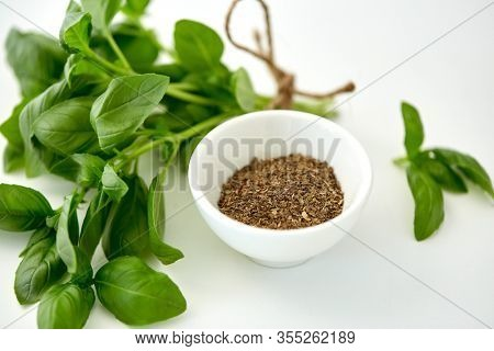 greens, culinary and flavoring concept - bunch of fresh basil herb and dry seasoning in cup on white background