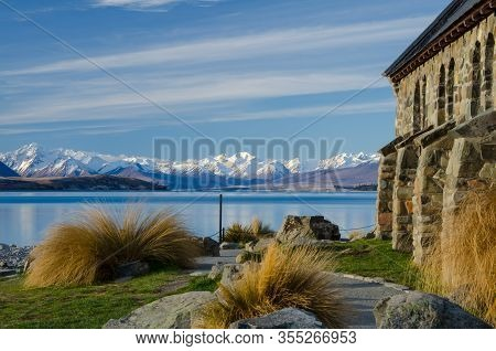 Lake Tekapo With Snow Covered Mountains In The Background And Church Of The Good Shepherd In The For