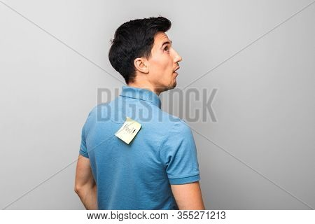 Stupid Looking Man In Blue Shirt With A Yellow Sticky Note With Word Fool On His Back Stupidly Looki