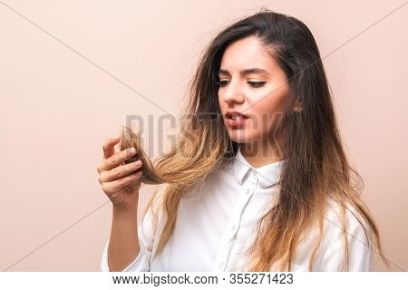 Hair Problems. Young Woman In White Shirt Checking Her Britle, Damaged, And Split Hairs Against Pink