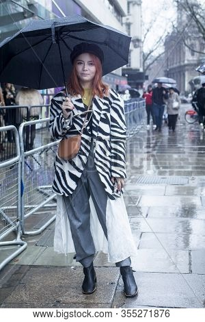 London, Uk- Febryary 15 2020: Fashionable People On The Street . Street Style. A Girl In A Jacket Wi