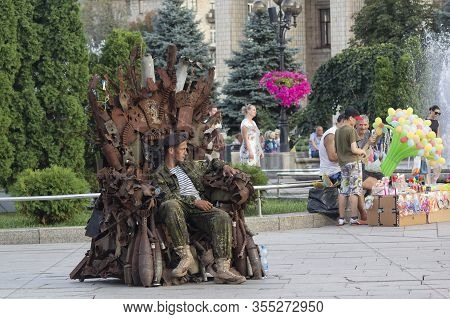 Kiev, Ukraine - July 28, 2019: Man In Military Uniform Sits On A Chair Made From Shrapnel Of Munitio