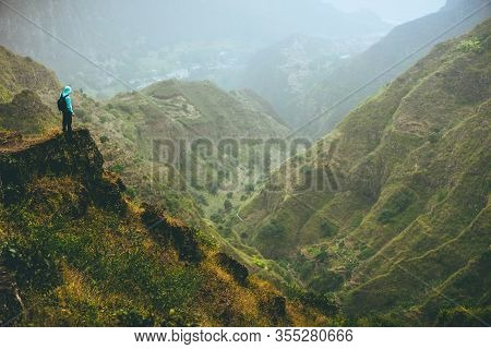 Male Hiker On Top Of The Mountain Rock With Gorgeous Panorama View Over High Mountain Ranges And Dee
