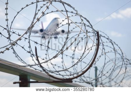 Fence With Razor Barbed Wire Protection Against Blue Sky Background. Dictatorship And Tyranny Concep
